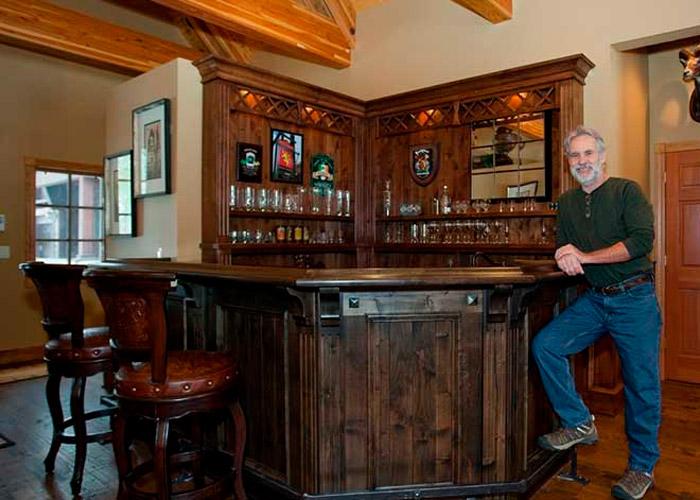 homem escorado no balcão de bar de madeira escuro