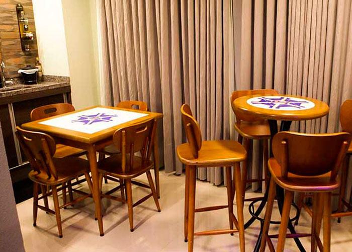 dois conjuntos de mesa de madeira com cadeiras e banquetas