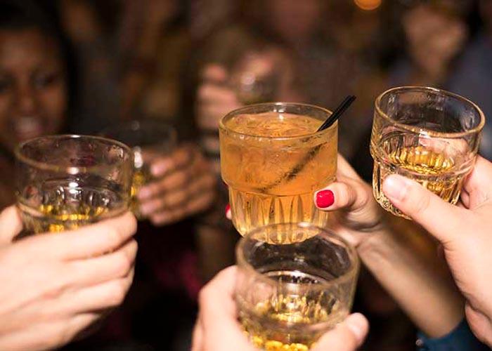 mãos segurando copos de drink levantadas em brinde