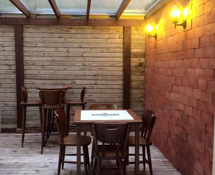 Parede de tijolos e madeira, piso também em madeira e iluminação amarela.