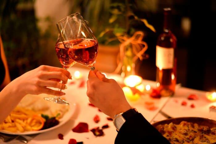 Casal brindando em uma mesa com pétala de rosas