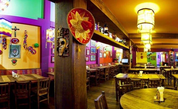 Restaurante com a decoração de caveira e chapéu mexicano pendurado na parede