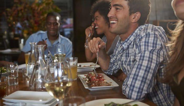 Clientes comendo e sorrindo em restaurante
