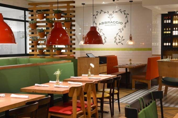 Restaurante italiano em tons vermelho, branco e verde, com mesas e cadeiras de madeira e painel de plantas.