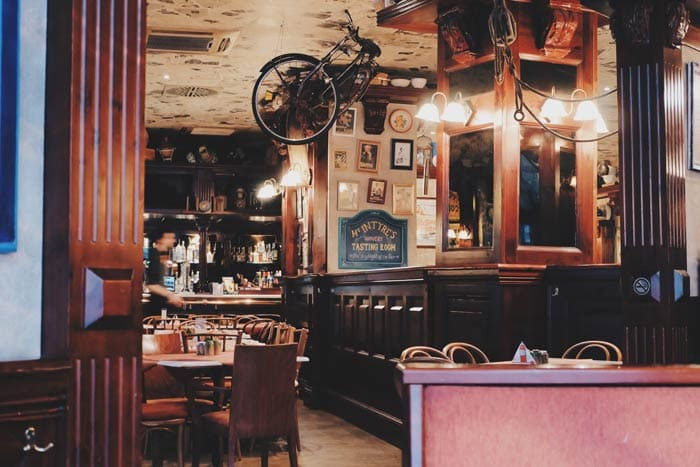 Decoração vintage na parede, quadros e bicicleta pendurada, móveis e pilares de madeira.