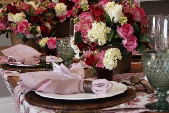 Mesa com pratos, taças, talheres, guardanapo e arranjos de flores