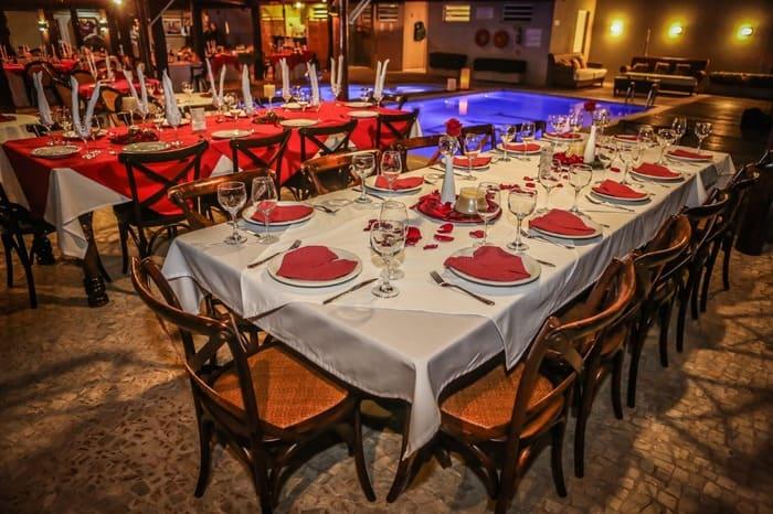 Mesas, cadeiras, pratos, taças, talheres, pétala de rosas e guardanapos vermelhos em forma de coração
