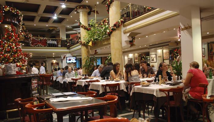 Restaurante com clientes em mesas, árvore de natal e demais enfeites natalinos pendurados.