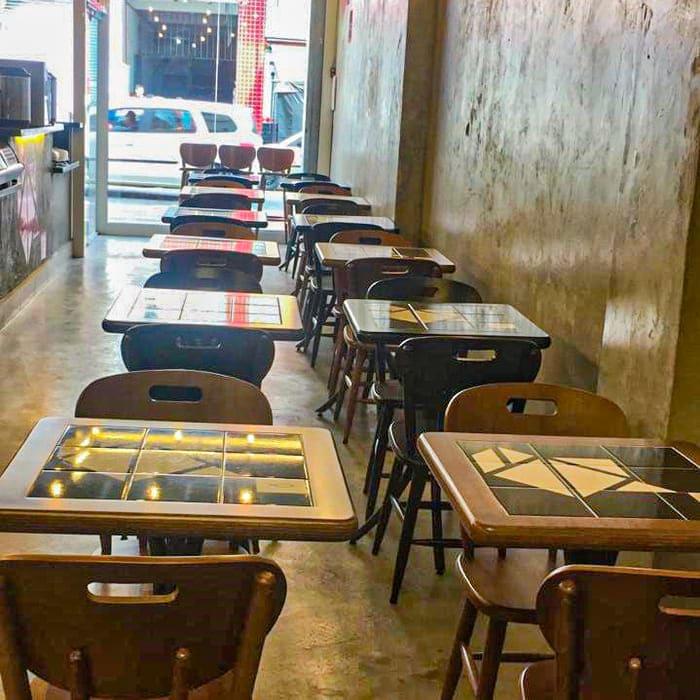 Restaurante com piso e parede em concreto aparente