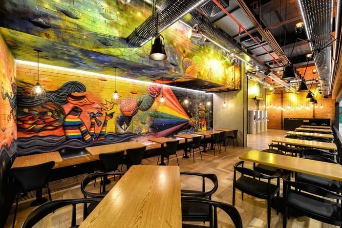 Grafite em parede de restaurante, mesas, cadeiras e luminárias.