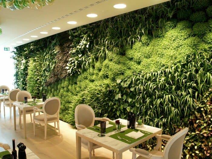 Mesas, cadeiras e jardim vertical na parede inteira de restaurante.