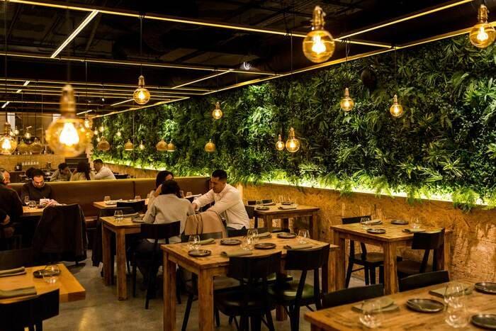Restaurante com jardim vertical na horizontal, mesas, cadeiras e pessoas comendo
