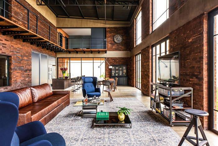 Loft Industrial com parede de tijolos, sofá, cadeiras, mesas e televisão