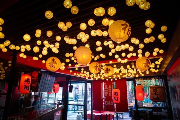 Luminárias vermelhas e amarelas no teto de restaurante japonês.