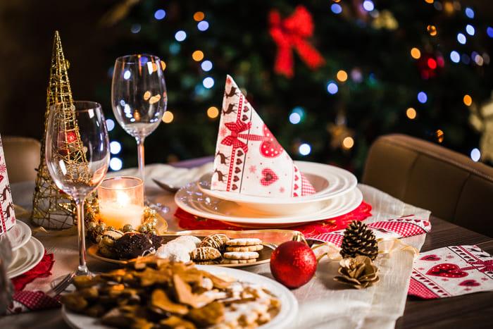 Mesa de natal com prato, guardanapo, taças, pinhas e bolas natalinas