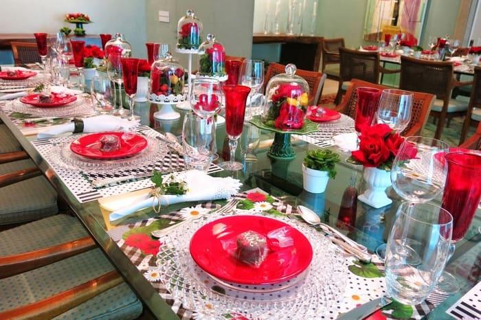 Mesa com louças em vermelho, pratos, taças, talheres, guardanapos e flores.