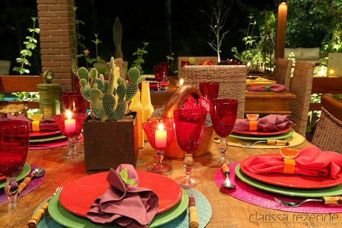 Mesa de restaurante mexicano com vaso com cacto, velas, pratos, taças e guardanapos coloridos.