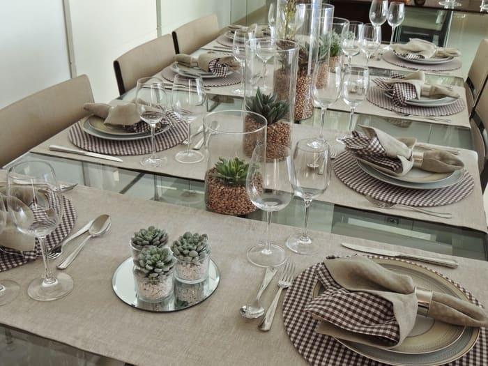 Mesa com suculentas, pratos, talheres, taças e guardanapos xadrez.
