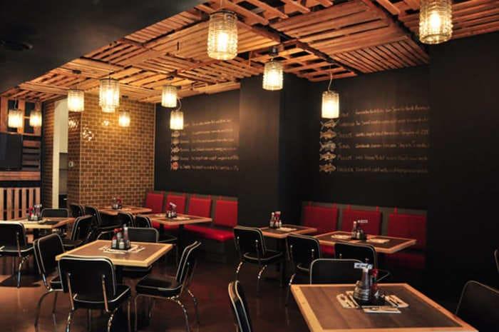 Restaurante Fish Shack com mesas, cadeiras e pallets de madeira no teto com luminárias penduradas