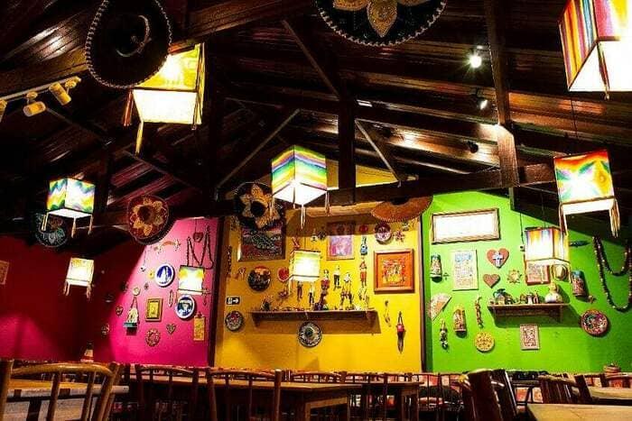 Restaurante mexicano com parede rosa, amarela e verde, com enfeites pendurados.