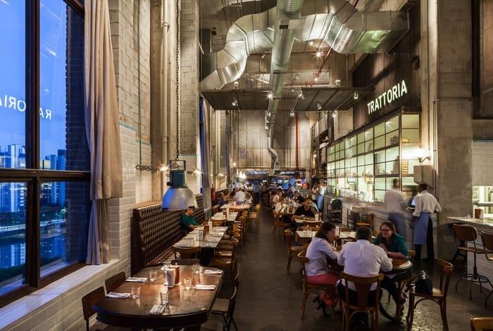 Arquitetura Industrial do restaurante Bráz Trattoria, tubulações e paredes de concreto aparente, janela, mesas e cadeiras
