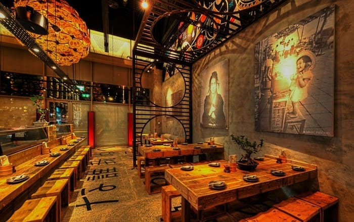 Restaurante japonês estilo rústico, com móveis de madeira, bonsais, e quadros na parede.