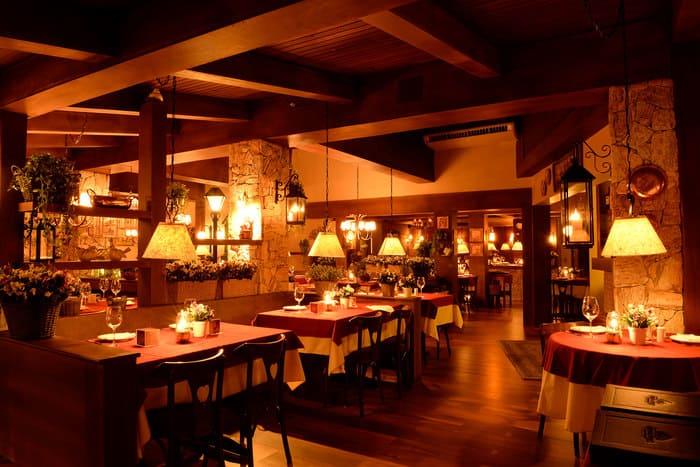 Restaurante com mesas, cadeiras, flores, e iluminação baixa no tom amarelo.