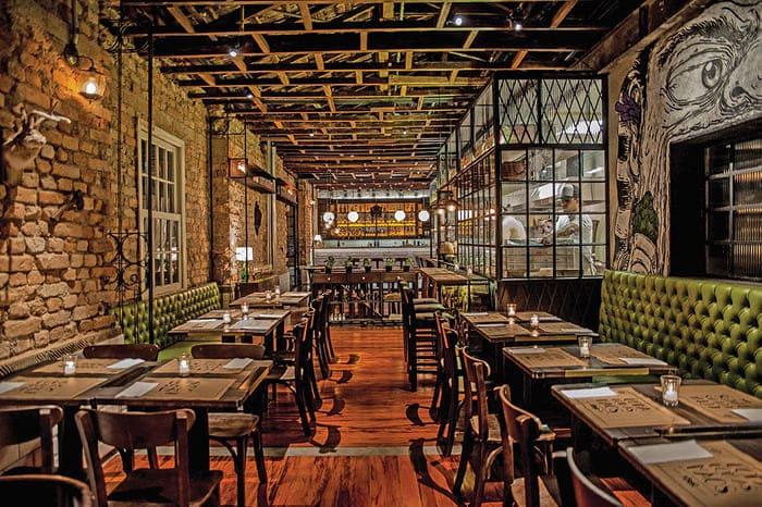 Parede de pedras, mesas e cadeiras no restaurante rústico Fôrno