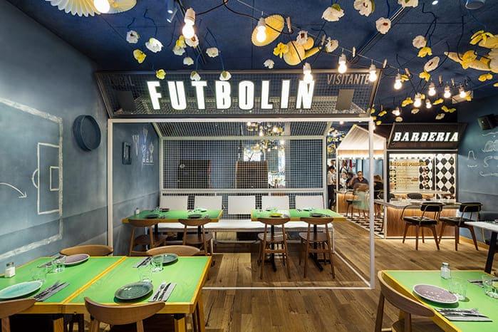 Restaurante do jogador Messi. Mesas verdes, cadeiras em maderia, parede de lousa e grades na decoração.