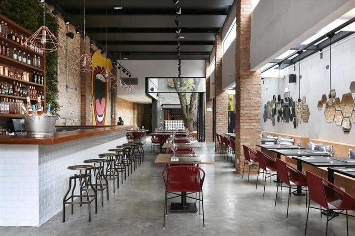 Restaurante Industrial MéZ com paredes revestidas de tijolos, banquetas, mesas e cadeiras