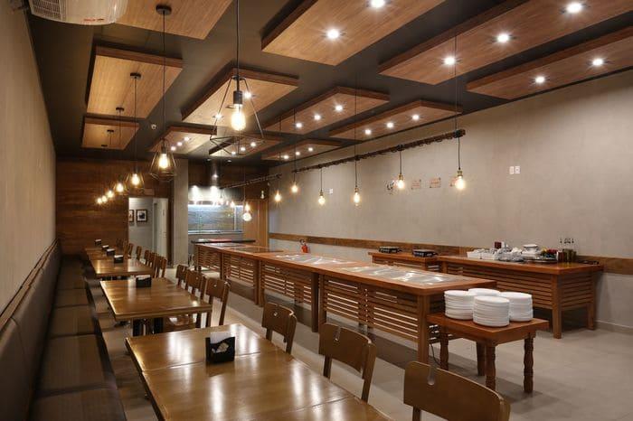 Restaurante Industrial com mesas e cadeiras de madeira, iluminação com pendulos de metal.