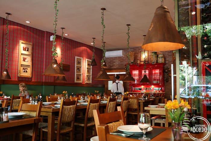 Per Voi Restaurante com mesas e cadeiras de madeira, luminárias suspensas e parede de tijolos