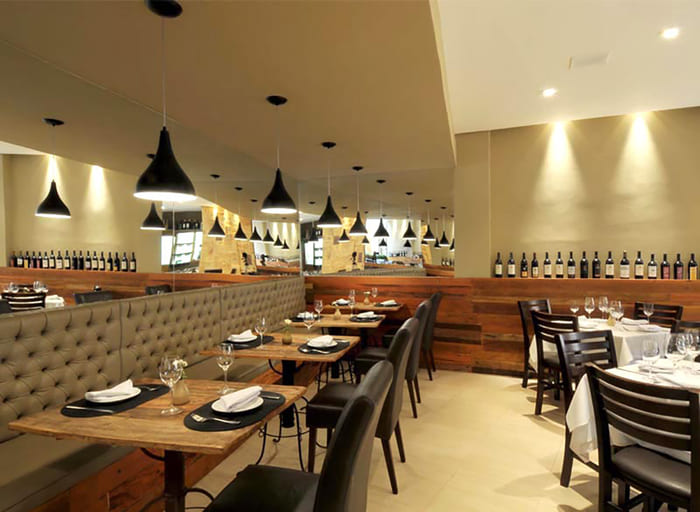 Restaurante com espelhos, assentos de canto, cadeiras de coro e mesas de madeira