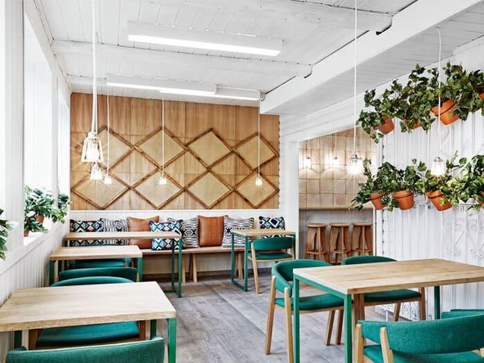 Restaurante com mesas, cadeiras, painel de madeira e jardim suspenso com plantas.
