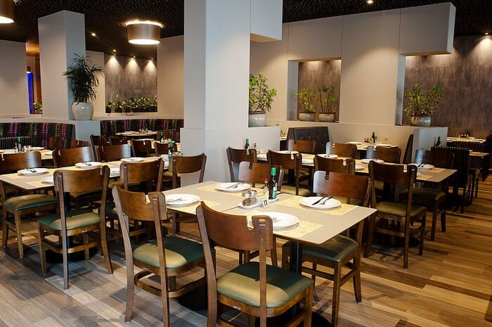 Restaurante com as paredes claras, mesas, cadeiras e vasos de planta