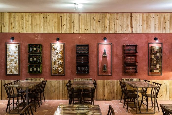 Restaurante rústico com parede, mesas e cadeiras de madeira