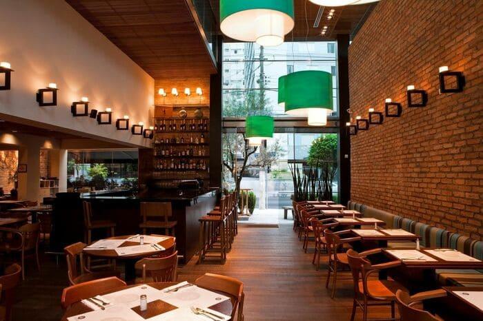 Parede de tijolinhos em restaurante rústico, porta de vidro, mesas e cadeiras