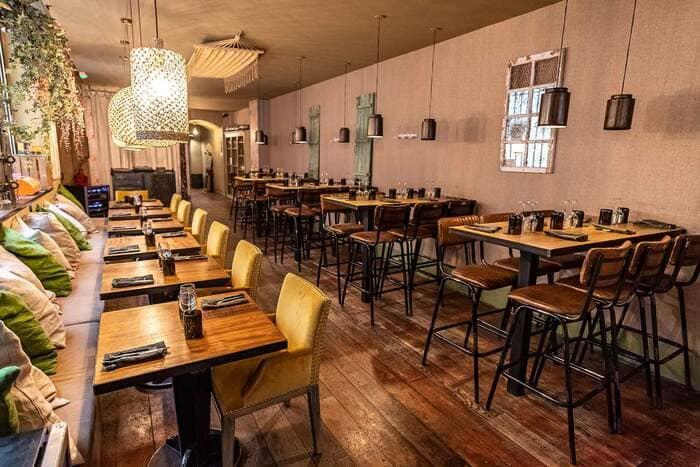 Restaurante vintage com paredes em tons pastéis, piso e mesas de madeira e cadeiras de metal e couro
