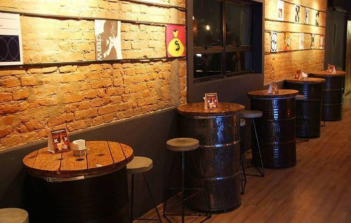 Ambiente com barris de metal como mesa e parede de tijolos