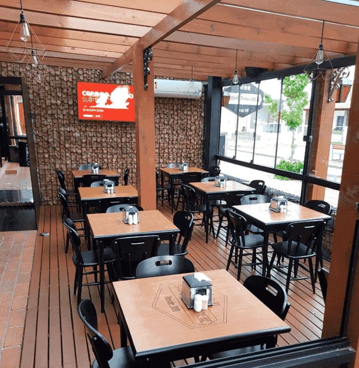 Deck rústico de restaurante com estruturas de madeira e parede decorada com lenhas