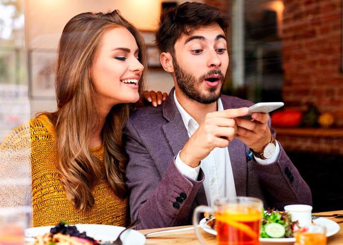 Mulher e Homem contentes fotografando o prato de comida