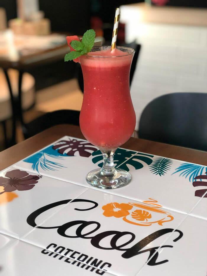 Mesa com azulejo colorido apoiando um copo com suco