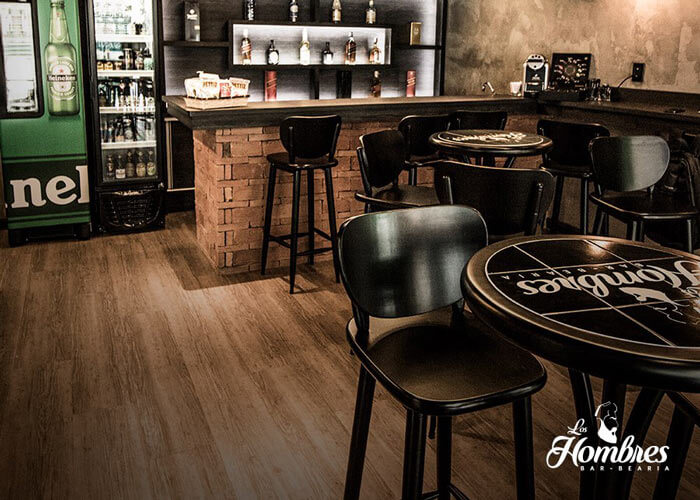 Ambiente interno com mesas de madeira pretas e banquetas