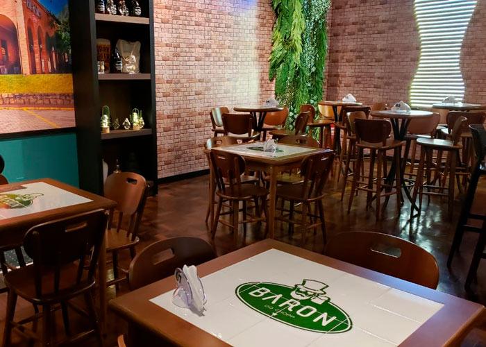 Ambiente interno com mesas de madeira e folhagem verde