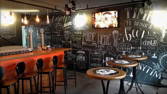 Banquetas, mesas, balcão, parede de giz e tv