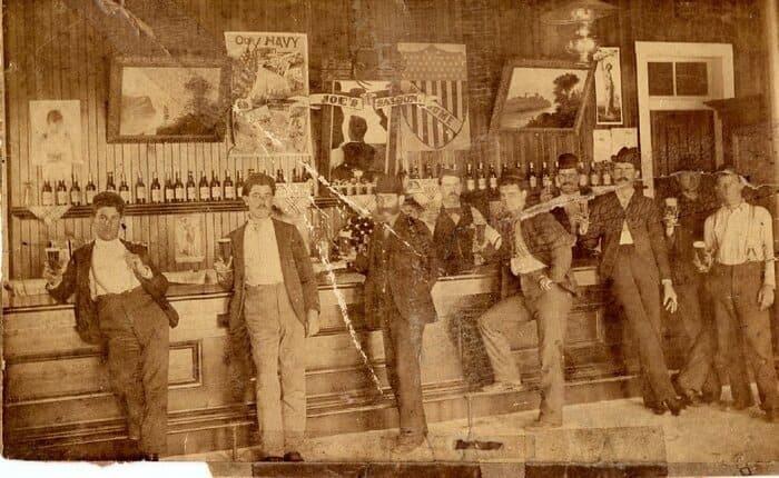 Homens escorados na barra de ferro na parte inferior do balcão de um bar