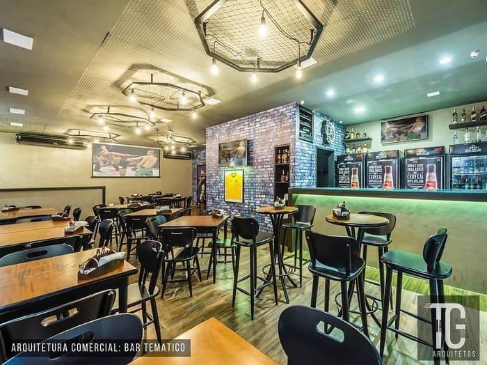 Mesas, cadeiras, banquetas, balcão e bebidas no bar temático Esportagem