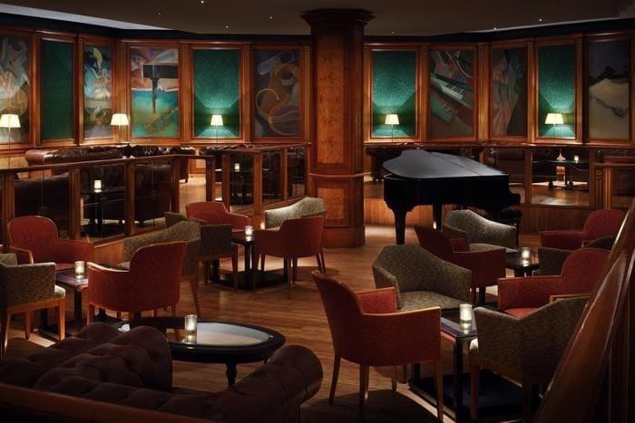Mesas, poltronas e piano em bar de hotel