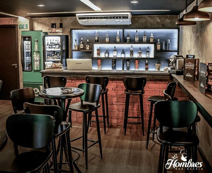 Mesas, banquetas, balcão e bebidas no Bar e Barbearia Los Hombres