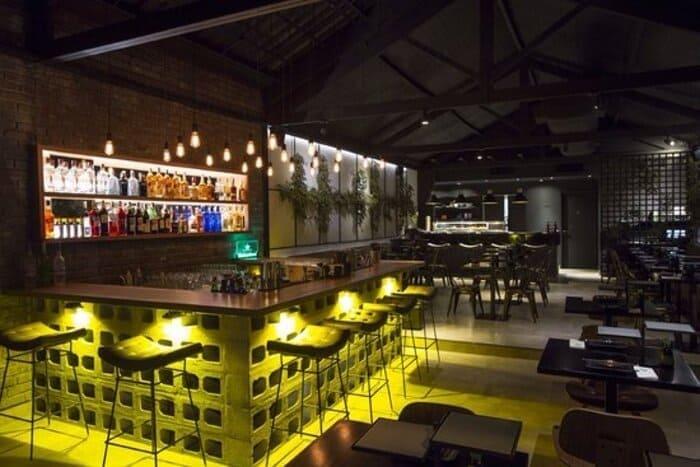 Mesas, cadeiras, balcão, banquetas e bebidas em prateleiras na parede em um sushi bar